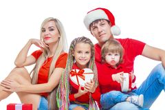 Family at Christmas. Cheerful family in Santa hats looking at camera and smiling while isolated on white. Portrait stock image