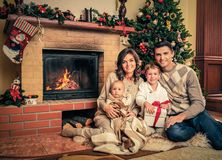 Family in Christmas decorated house interior. Family near fireplace in Christmas decorated house interior with gift box Stock Image