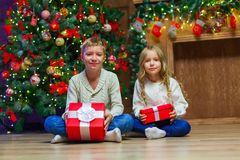 Family on Christmas eve at fireplace. Kids opening Xmas presents stock image