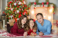 Family on Christmas eve at fireplace. Kids opening Xmas presents. Children under Christmas tree with gift boxes. Decorated living Royalty Free Stock Photography