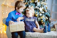 Older brother and little sister opening gift in Christmas living room royalty free stock photo