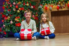Family on Christmas eve at fireplace. Kids opening Xmas presents royalty free stock photography