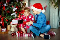 Family on Christmas eve at fireplace. Kids opening Xmas presents. Children under Christmas tree with gift boxes royalty free stock photos