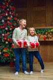 Family on Christmas eve at fireplace. Kids opening Xmas presents royalty free stock image