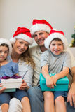 Family in Christmas hat holding presents on sofa Royalty Free Stock Photos
