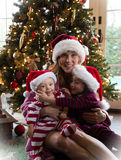 Family Christmas. Mom, Daughter, and Son sitting in front of a Christmas Tree Royalty Free Stock Images