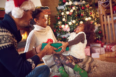 Family on Christmas opening gifts sitting on floor at home Royalty Free Stock Photography