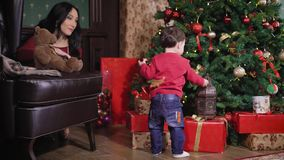 Family of a Christmas photographic studio. The woman tries to interest the child. The kid has seen a big iron cage under stock video