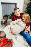 Family Christmas portrait. Smiling man is hugging his beautiful pregnant wife at home. stock photos