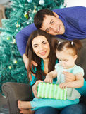 Family with Christmas present near the Christmas tree Royalty Free Stock Photography
