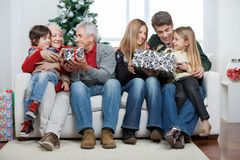 Family With Christmas Presents Sitting In House Stock Photography