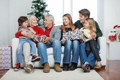Family With Christmas Presents Sitting On Sofa Royalty Free Stock Photos