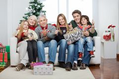 Family With Christmas Presents Sitting On Sofa Stock Photography