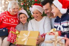 Family with Christmas presents. Smiling family at Christmas time holding lots of presents at home Stock Photo