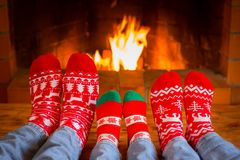 Family in Christmas socks near fireplace royalty free stock photography