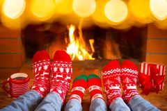 Family in Christmas socks near fireplace Stock Image