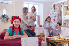Family at Christmas Time. Three Generation Family at Christmas Time. Young Girl is looking at the Camera and Smiling while the family chat in the background Stock Photo