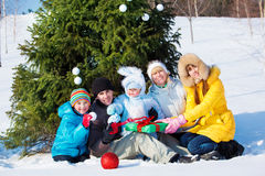 Family beside Christmas tree Stock Photos