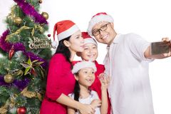 Family with Christmas tree taking selfie Royalty Free Stock Image