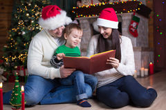 Family, christmas, x-mas, concept - smiling parents in santa hats and son kid reading book Royalty Free Stock Photos