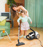 Family cleaning home with vacuum cleaner Royalty Free Stock Image