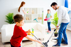 Family cleaning house. Happy family of four is cleaning their house Stock Images