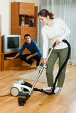 Family  cleaning with vacuum cleaner in home Stock Image