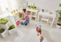 Family cleans the room. Happy family cleans the room. Mother and daughter do the cleaning in the house. A young women and a little child girl dusting royalty free stock photo