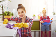 Family cleans the room. Happy family cleans the room. Mother and daughter do the cleaning in the house. A young women and a little child girl dusting royalty free stock images