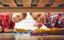 Family cleans the room. Happy family cleans the room. Mother and daughter do the cleaning in the house. A young women and a little child girl wiped the floor royalty free stock photo
