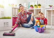 Family cleans the room. Happy family cleans the room. Mother and daughter do the cleaning in the house. A young women and a little child girl wiped the dust and royalty free stock image