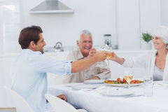 Family clinking their glasses of white wine Stock Images