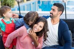 Family close to the pool. Beautiful latin family relaxing close to the pool Royalty Free Stock Image