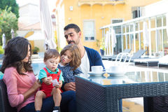 Family close to the pool. Beautiful latin family relaxing close to the pool Royalty Free Stock Photo