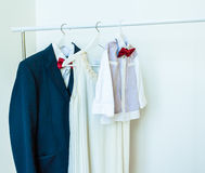 Family clothes. Baby shirt, red bow tie, women`s dress, mens shirt Stock Photo