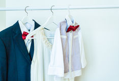 Family clothes. Baby shirt, red bow tie, women`s dress, mens shirt Royalty Free Stock Images