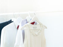 Family clothes. Women`s dress, children`s shirt and man`s shirt on a hanger Royalty Free Stock Photo