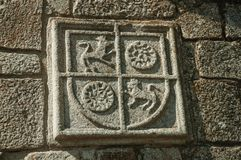 Family coat of arms carved on stone in a medieval chapel. Charming family coat of arms carved on stone in a wall of medieval chapel, in a sunny day at Belmonte stock images