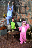 Family in colorful costumes of dragons pose in very old room. With table and samovar Stock Photos