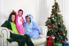 Family in colorful costumes of dragons sit on sofa. Near Christmas tree Royalty Free Stock Images