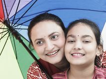 Family with a colourful umbrella. Mother and daughter with a colourful umbrella royalty free stock photos