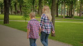 Family communication loving mom son walking park. Family communication and loving relationship. Mother and son walking in the park stock footage
