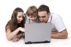 Family and computer. Young family lying on a floor with the computer on white isolation stock image