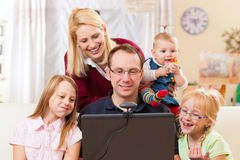Family with computer having video conference. Young family in front of computer with camera having a video chat Royalty Free Stock Photography