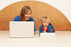 Family with computer at home. Mother and little son working with computer from home Stock Photos