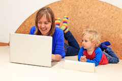 Family with computer at home. Mother and little son working with computer from home Royalty Free Stock Photo