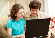 Family Computer Time. Teen girl and her mom using the computer together Royalty Free Stock Photo