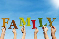 Family concept. Group of people are holding Family letters under bright blue sky royalty free stock images