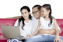 Family sitting on sofa with laptop. Family concept. Happy family sitting on the sofa while using a laptop computer together Stock Images