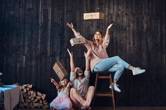 Family concept. Mom, dad and daughter together with gifts in empty room against the wooden wall. Family concept. Happy Mom, dad and daughter together with gifts royalty free stock images
